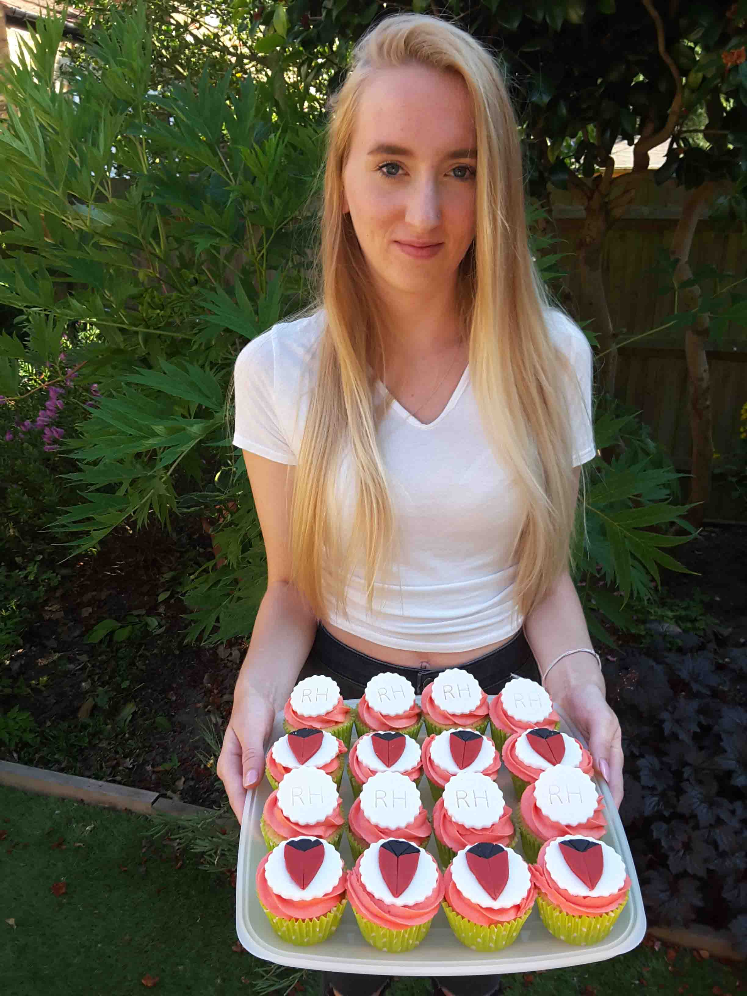 Photo of young woman holding tray of cupcakes decorated with Chelsea Pensioner shield
