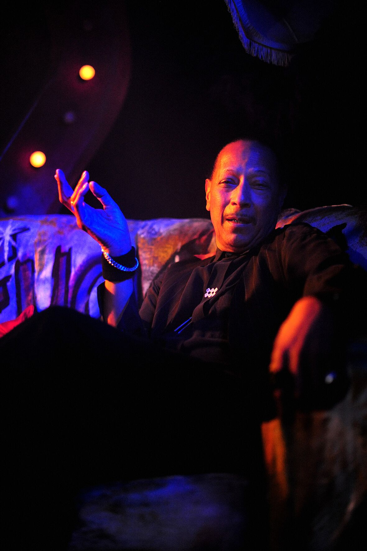 Singer Peter Straker sitting under blue lights