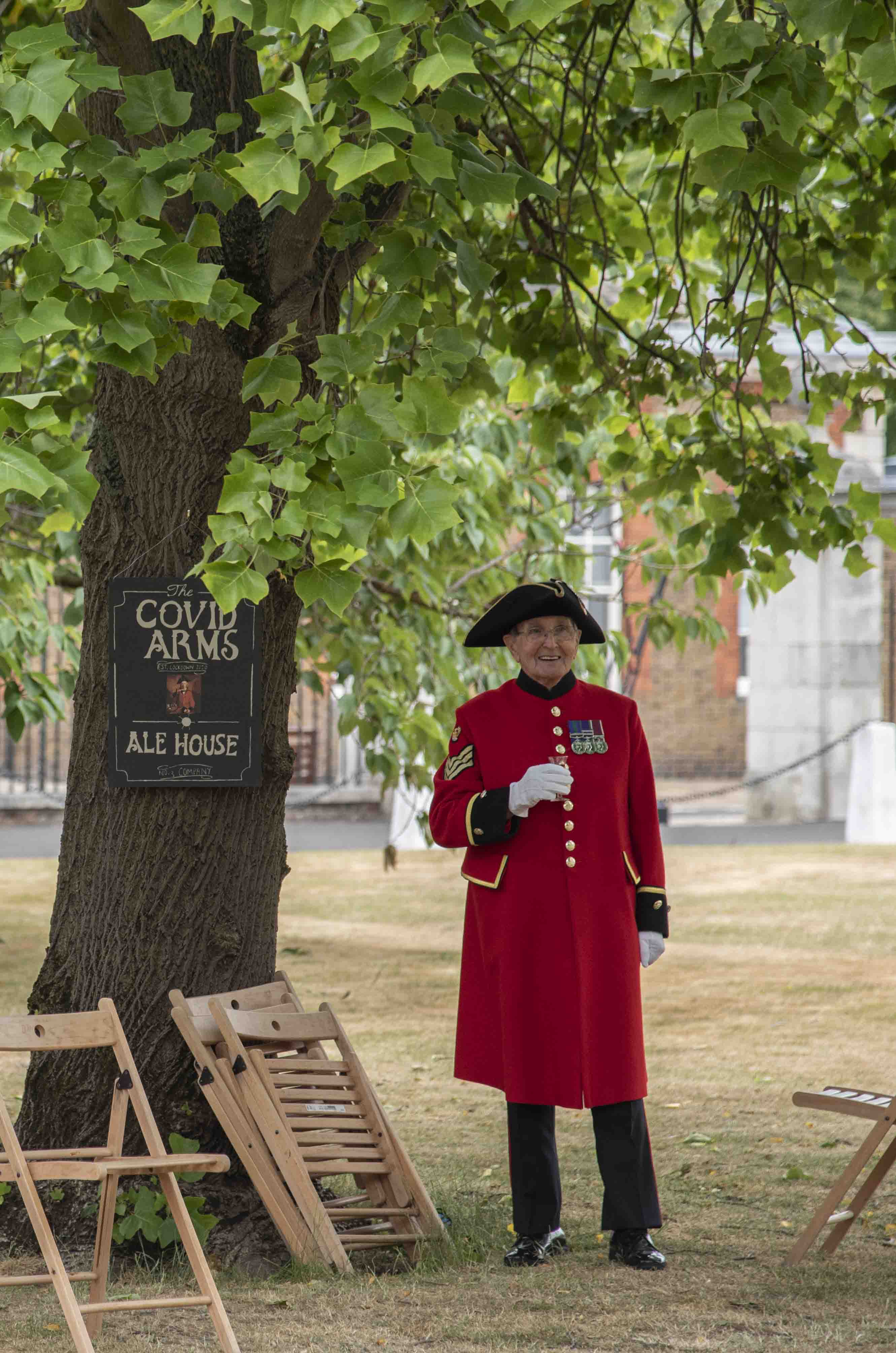 A Pensioner enjoying a drink following the Founder's Day Parade under a tree with a sign affixed reading 'the COVID Arms'