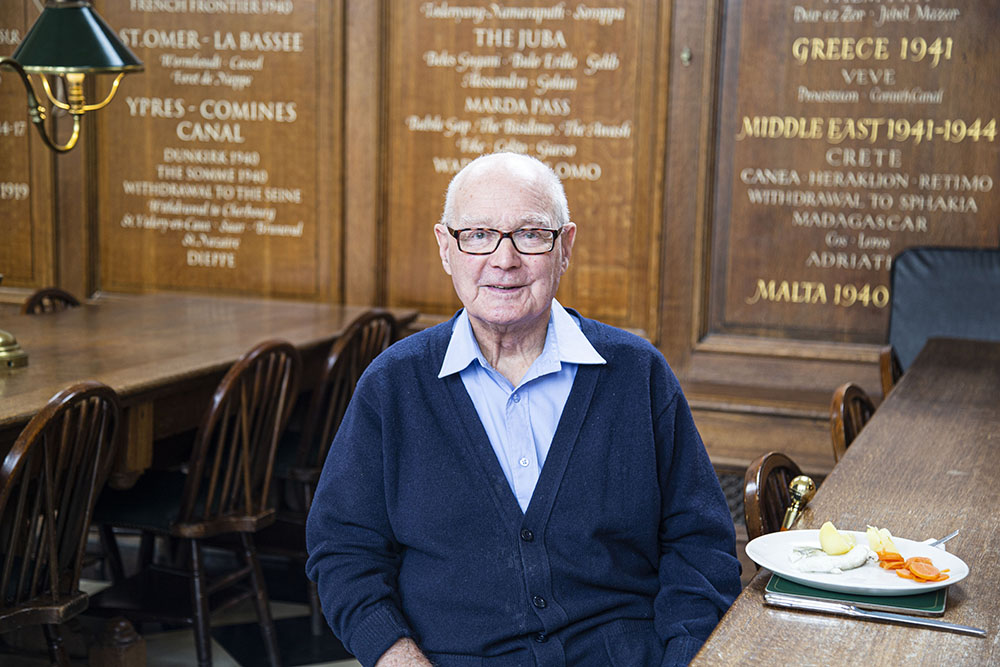 A Chelslea Pensioner sitting at the table in the Great Hall during lunchtime