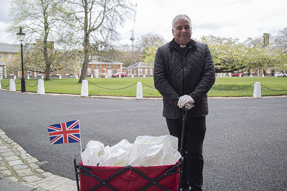 Our Chaplain, Rev. Steven Brookes, in front of cart carrying medication with the British flag as he volunteers for the medication run