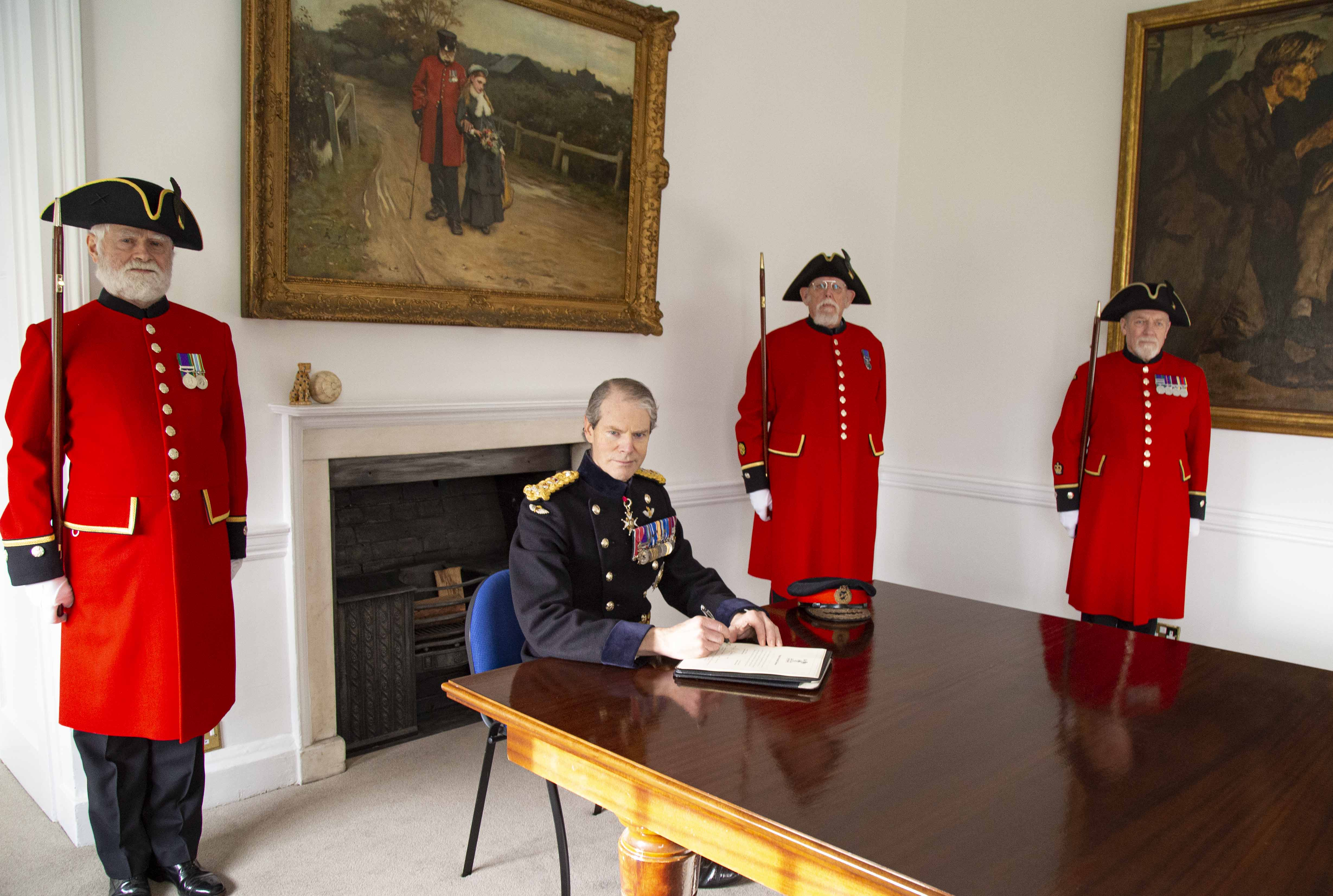 The Governor, General Sir Adrian Bradshaw and Pensioners witness the signing of the Armed Forces Covenant
