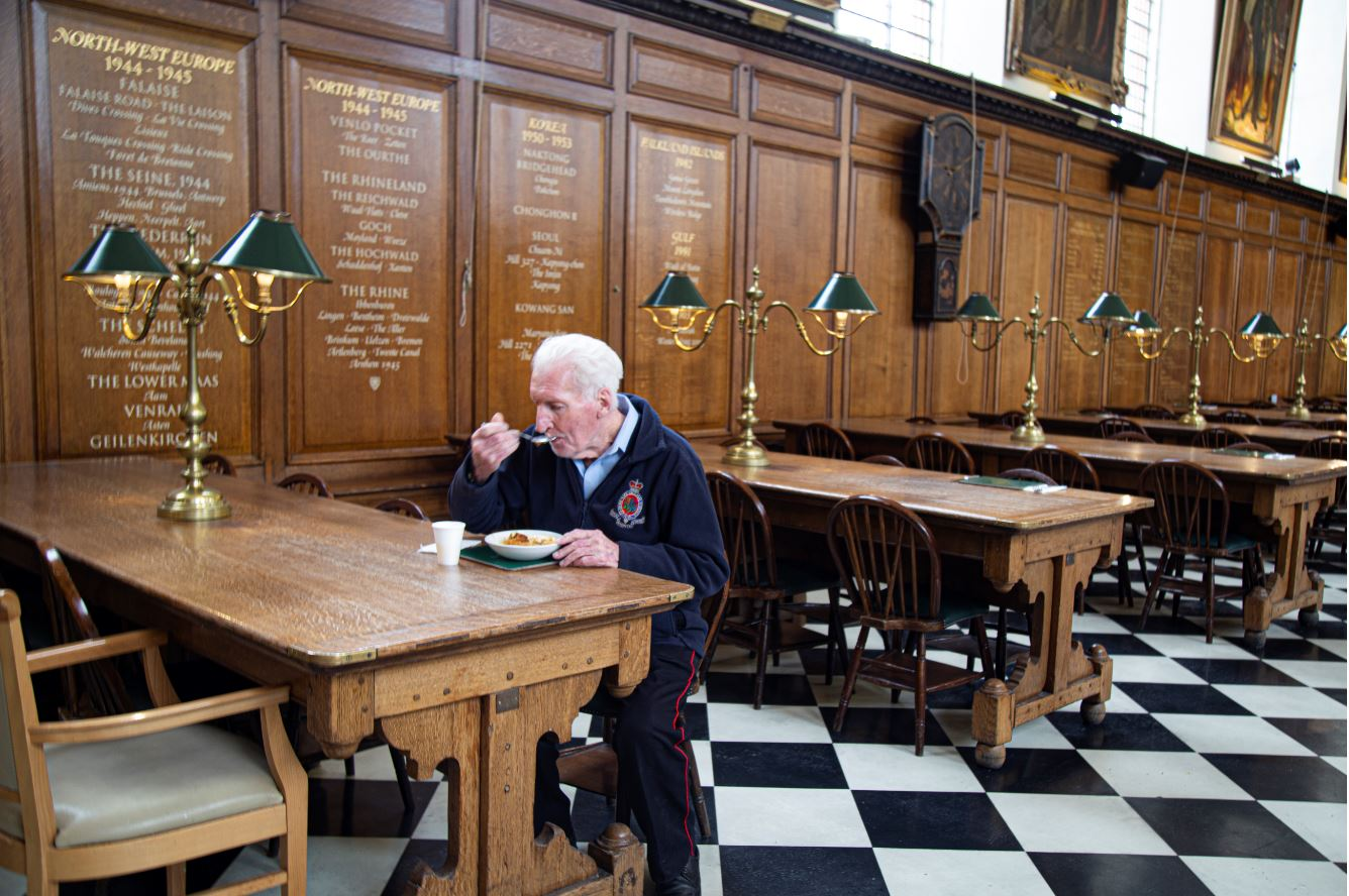 A Pensioner eating alone at a table in the Hospital's Great Hall